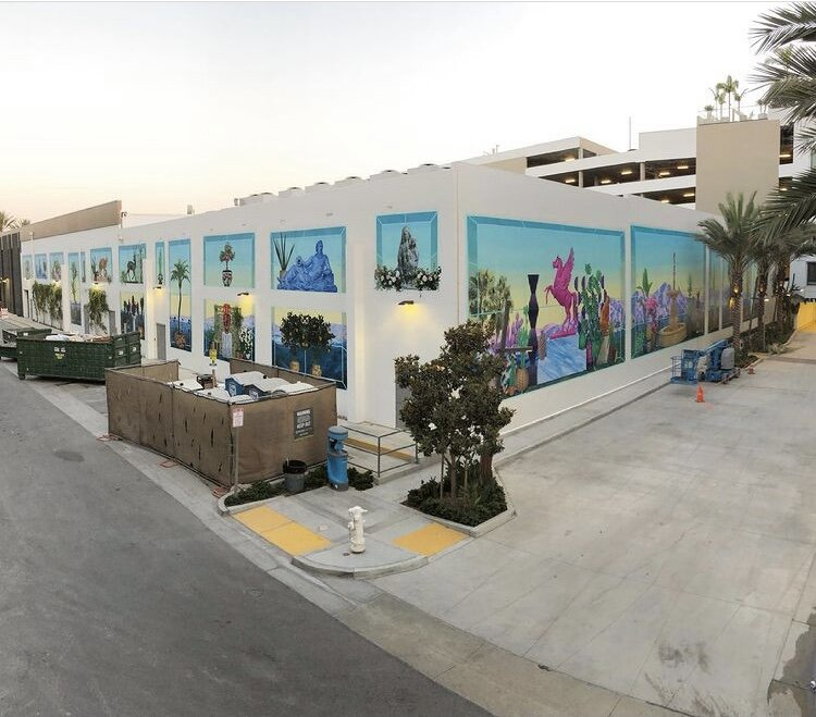 Street view of two sides of a building with a mural by Robert Minervini painted on both sides