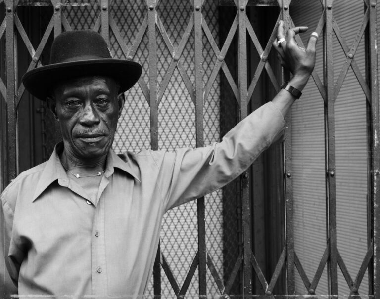Photograph of a man with hand on gate by Dawoud Bey